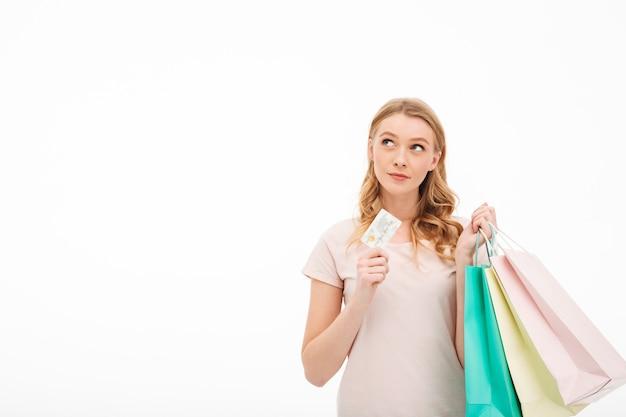 Jovem concentrada segurando o cartão de débito e sacolas de compras.