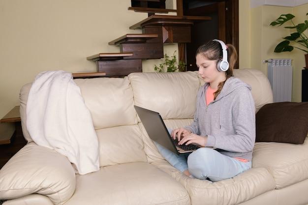 Jovem concentrada usando fones de ouvido e um laptop sentado no sofá