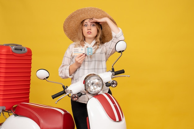 Jovem concentrada usando um chapéu recolhendo sua bagagem sentada em uma motocicleta e mostrando a passagem olhando algo com atenção