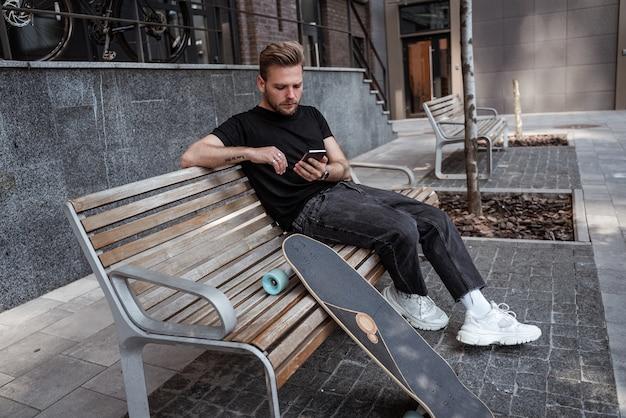 Jovem concentrado com longboard usando smartphone, navegando na internet, lendo notícias, curtindo postagens, sentado no banco no espaço da cidade moderna. conceito de lazer ao ar livre. skatista moderno.