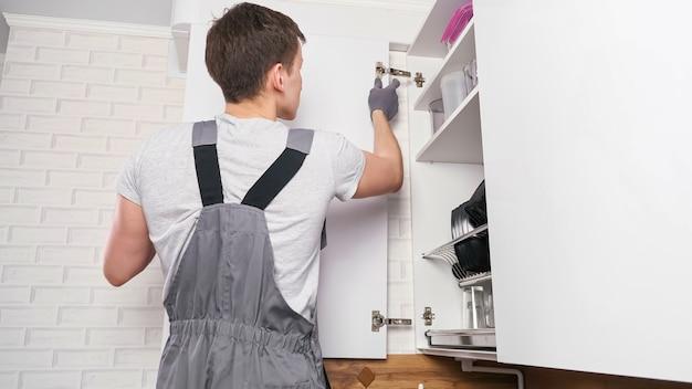 Jovem concentrado em um macacão cinza instala a porta do armário branco, torcendo parafusos nas dobradiças em uma cozinha contemporânea próxima à vista traseira
