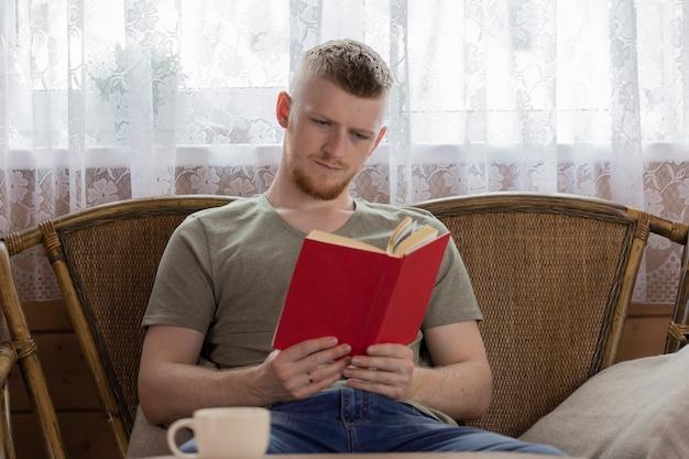 Jovem concentrado lendo um livro com capa vermelha em um banco de vime em uma casa de madeira do campo