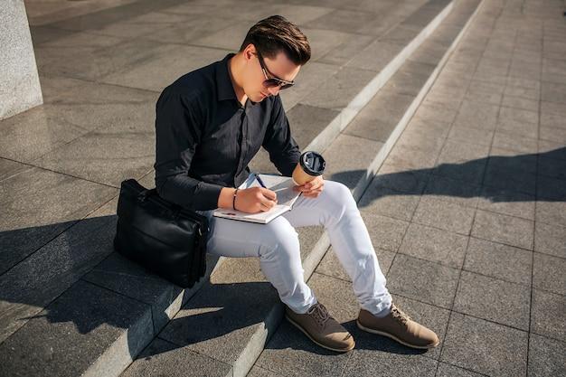 Jovem concentrado sentar nos degraus na rua e escrever no caderno. ele segura a xícara de café na mão. cara olha através dos óculos. está ensolarado lá fora.