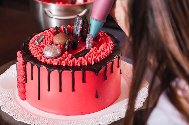 Jovem confeiteira decorando um bolo colorido com chocolate