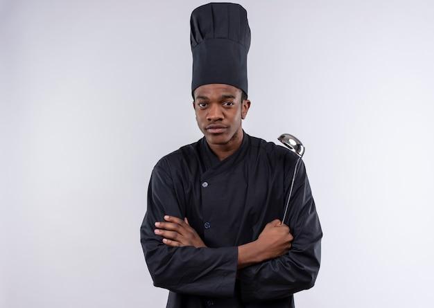 Jovem confiante afro-americana com uniforme de chef cruza os braços e segura a concha isolada no fundo branco com espaço de cópia