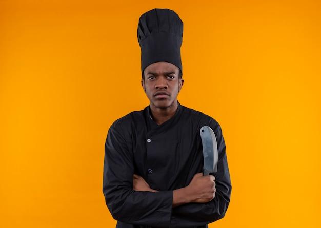 Jovem confiante afro-americana com uniforme de chef cruza os braços e segura uma faca isolada em um fundo laranja com espaço de cópia