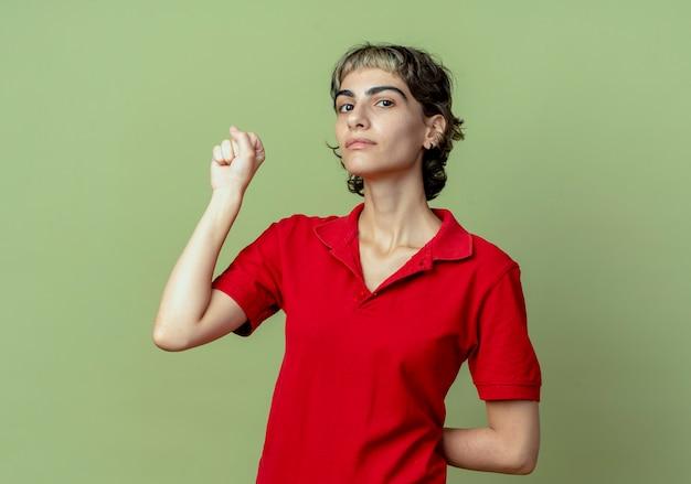 Jovem confiante caucasiana com corte de cabelo de duende cerrando o punho e escondendo a outra mão nas costas, isolada em um fundo verde oliva com espaço de cópia