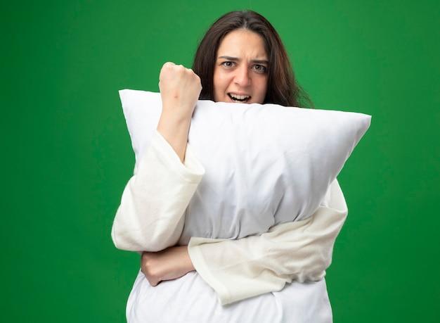 Jovem confiante caucasiana doente vestindo um manto abraçando o travesseiro, olhando para a câmera, fazendo um gesto forte isolado em um fundo verde com espaço de cópia