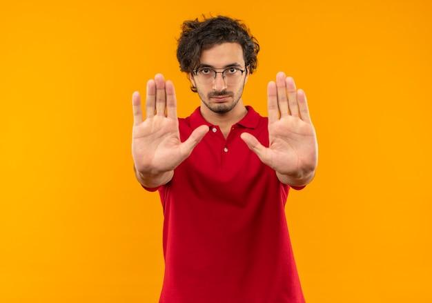 Jovem confiante de camisa vermelha com óculos óticos, gestos parados com as mãos isoladas na parede laranja