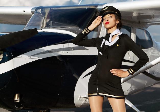 Jovem confiante e bela mulher piloto ou aeromoça na frente de um pequeno avião