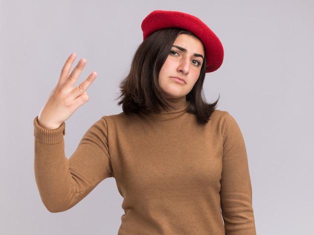 Jovem confiante e bonita caucasiana com chapéu boina gestos três com os dedos isolados na parede branca com espaço de cópia