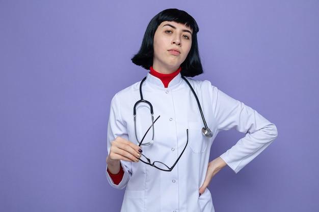 Jovem confiante e bonita caucasiana com uniforme de médico com estetoscópio segurando óculos ópticos e