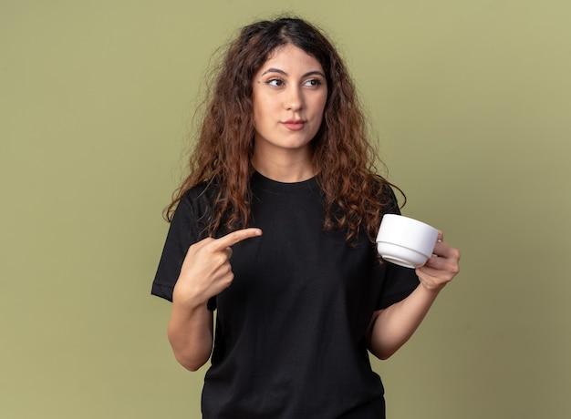 Jovem confiante e bonita caucasiana segurando e apontando para uma xícara de chá, olhando para o lado