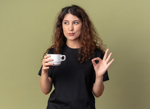 Jovem confiante e bonita caucasiana segurando uma xícara de chá, olhando para o lado, fazendo sinal de ok