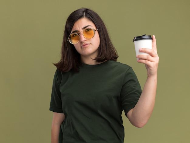 Jovem confiante e bonita caucasiana usando óculos de sol, segurando um copo de papel isolado na parede verde oliva com espaço de cópia