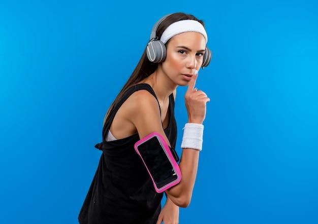 Jovem confiante e bonita desportiva usando bandana e pulseira e fones de ouvido com braçadeira de telefone em pé na vista de perfil gesticulando silêncio isolado na parede azul