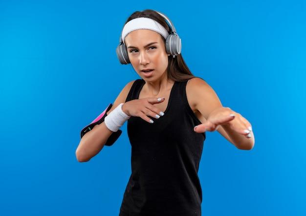 Jovem confiante e bonita desportiva usando bandana e pulseira e fones de ouvido com braçadeira de telefone, estendendo as mãos olhando para o lado isolado na parede azul