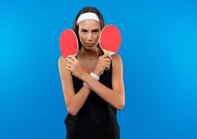 Jovem confiante e bonita desportiva usando bandana e pulseira segurando raquetes de pingue-pongue isoladas na parede azul com espaço de cópia