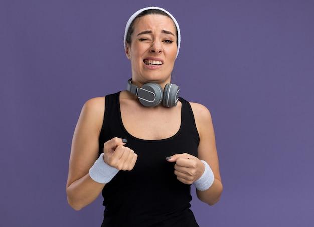 Jovem confiante e bonita esportiva usando bandana e pulseiras com fones de ouvido em volta do pescoço cerrando os punhos com um olho fechado isolado na parede roxa com espaço de cópia