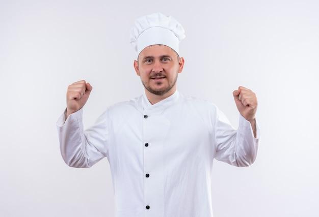Jovem confiante e bonito cozinheiro com uniforme de chef gesticulando forte e isolado na parede branca