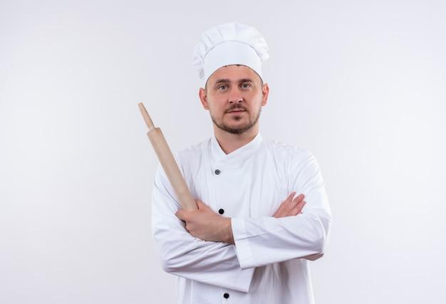 Jovem confiante e bonito cozinheiro em uniforme de chef em pé com a postura fechada e segurando o rolo de massa isolado na parede branca