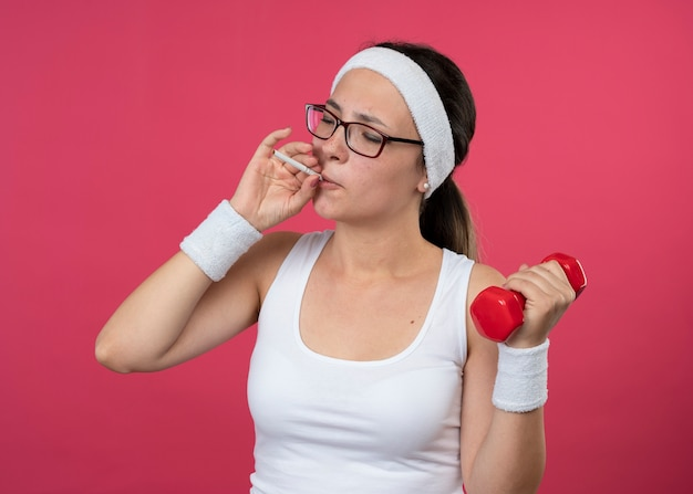 Jovem confiante e desportiva com óculos ópticos, bandana e pulseira, segurando halteres e fingindo fumar