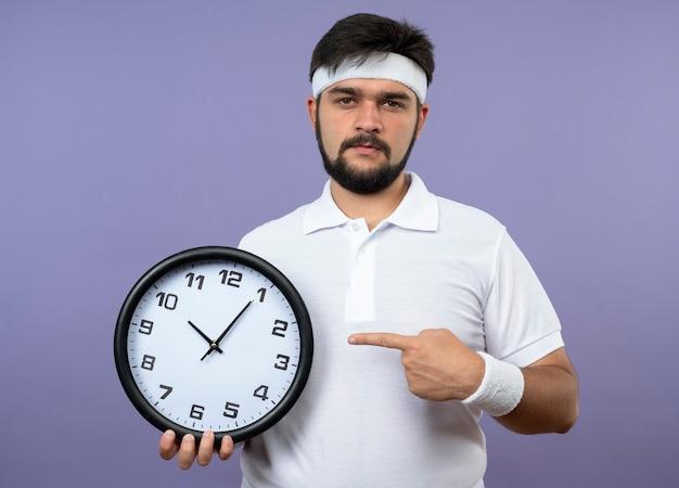 Jovem confiante e desportivo com fita na cabeça e pulseira segurando e aponta para o relógio de parede