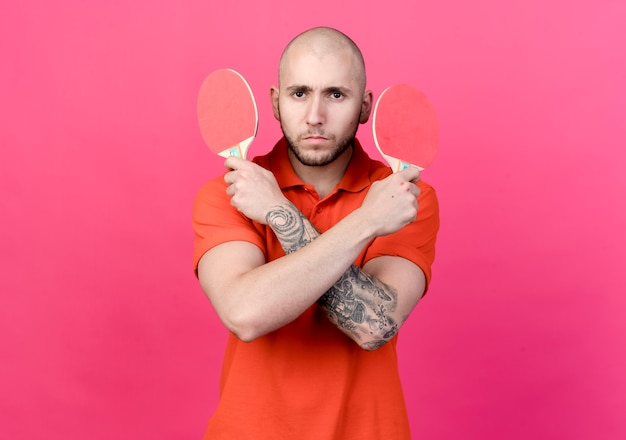Jovem confiante e desportivo segurando e cruzando uma raquete de pingue-pongue isolada na parede rosa