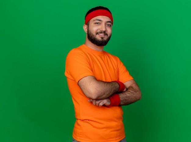 Jovem confiante e esportivo usando bandana e pulseira, cruzando as mãos isoladas no verde
