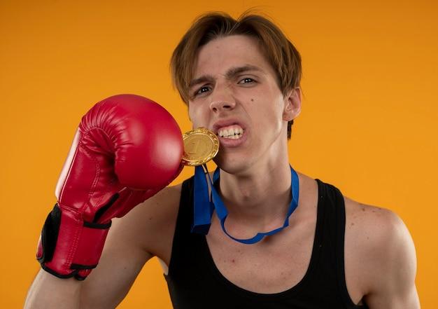 Jovem confiante e esportivo usando luvas de boxe e segurando uma medalha isolada na parede laranja