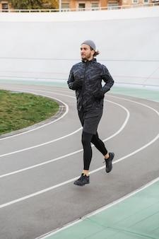 Jovem confiante em forma desportista correndo na pista de corrida ao ar livre do estádio