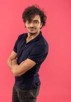 Jovem confiante em uma camisa preta com óculos ópticos cruza os braços e parece isolado na parede rosa