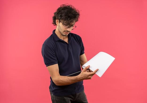 Jovem confiante em uma camisa preta com óculos ópticos segura e olha para a área de transferência isolada na parede rosa