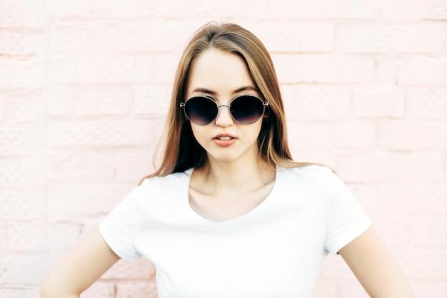 Jovem confiante em uma camiseta branca e óculos escuros em um fundo rosa