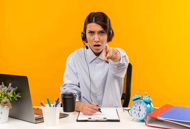 Jovem confiante em uma central de atendimento usando fone de ouvido, sentada na mesa, segurando uma caneta e apontando isolado em laranja