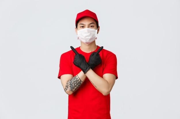 Jovem confiante entregador de camiseta vermelha e boné, use luvas e máscara médica para entregar as encomendas na casa do cliente durante a covid-19, mostrando variantes, apontando para o lado, duas opções