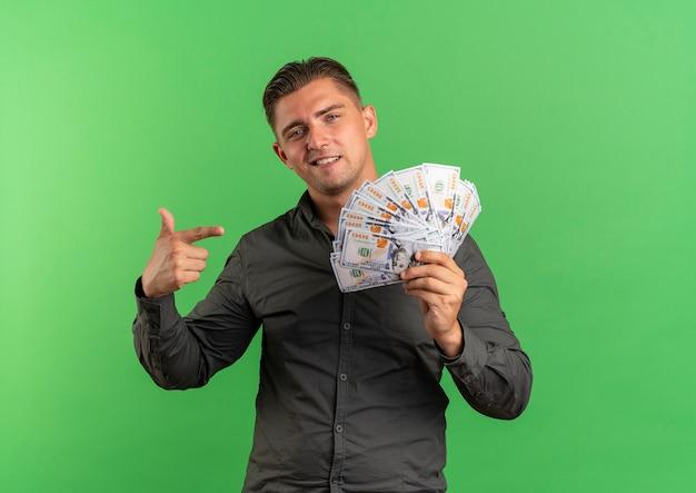 Jovem confiante loira bonita segurando e apontando dinheiro isolado em um fundo verde com espaço de cópia