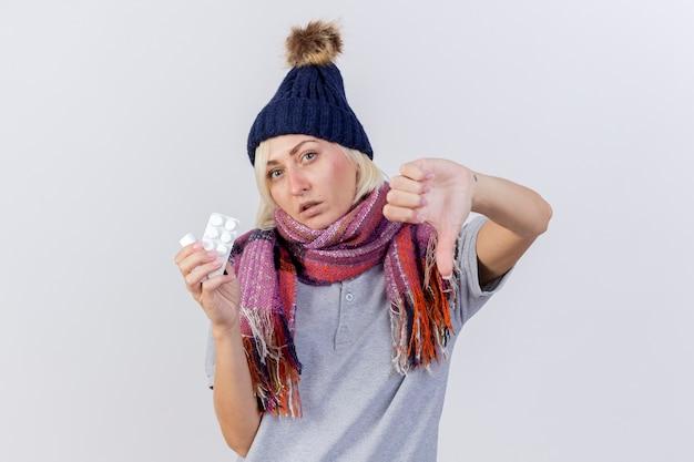 Jovem confiante loira doente, mulher eslava usando chapéu de inverno e lenço com os polegares para baixo e segurando remédio em frasco de vidro com pacote de comprimidos isolados na parede branca com espaço de cópia