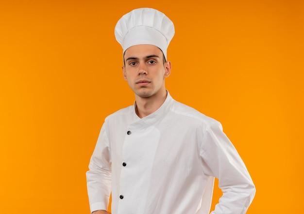 Jovem confiante masculino legal vestindo uniforme de chef - na parede amarela isolada com espaço de cópia