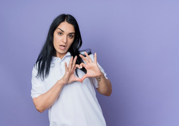 Jovem confiante morena caucasiana gesticulando sinal de coração com a mão isolado na parede roxa