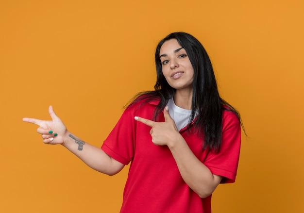 Jovem confiante morena caucasiana, vestindo uma camisa vermelha apontando para o lado com duas mãos isoladas na parede laranja