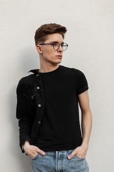 Jovem confiante retrato fresco com penteado em roupas da moda jeans preta em óculos elegantes perto da parede ao ar livre. modelo de cara bonito na moda descansando na rua. moda masculina casual. estilo de rua.