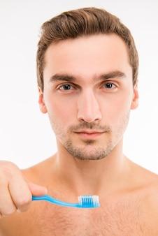 Jovem confiante segurando uma escova de dentes