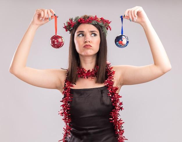 Jovem confusa, bonita, caucasiana, usando coroa de flores de natal e guirlanda de ouropel em volta do pescoço segurando enfeites de natal perto da cabeça, olhando para um deles isolado no fundo branco
