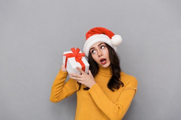 Jovem confusa com um chapéu de natal em pé, isolada sobre um fundo cinza, segurando uma caixa de presente