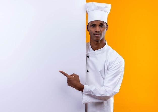 Jovem confusa cozinheira afro-americana com uniforme de chef fica atrás de uma parede branca e aponta para uma parede isolada em uma parede laranja