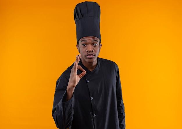 Jovem confusa cozinheira afro-americana em uniforme de chef gesticulando com a mão ok sinal isolada na parede laranja