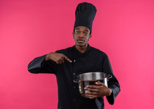 Jovem confusa cozinheira afro-americana em uniforme de chef segura e aponta para uma panela isolada na parede rosa