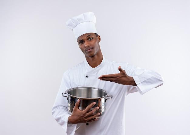 Jovem confusa cozinheira afro-americana em uniforme de chef segura e aponta para uma panela na parede branca isolada