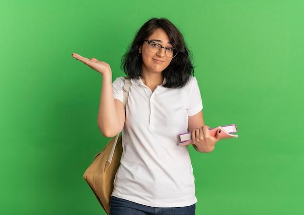 Jovem confusa e bonita caucasiana colegial usando óculos e bolsa traseira segura livros e levanta a mão no verde com espaço de cópia